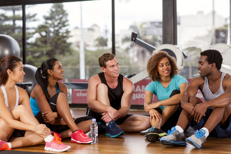 Multi-ethnic group relaxing before their gym glass