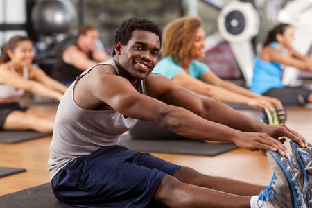 clases: Hombre afroamericano joven que estira en un gimnasio y mirando a la c�mara