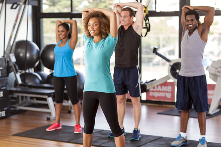stretching: Multi-ethnic group stretching in a gym before their exercise class Stock Photo