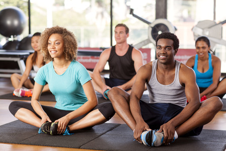 Multi-ethnic group stretching in a gym before their exercise class Stock Photo