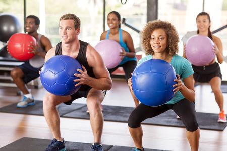 grupo de personas: Multi�tnico clase de gimnasia haciendo sentadillas con balones medicinales