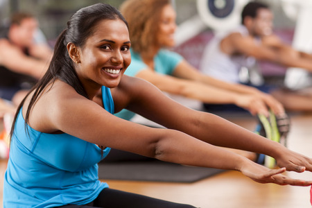 Young Indian woman stretching in a gym and looking to camera