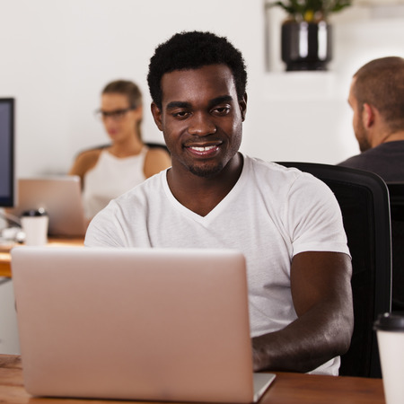 Young African American entrepreneur working on a laptop in a tech startup office Stock Photo