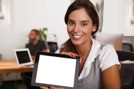 Young woman entrepreneur displaying her tablet computer in her startup office Stock Photo