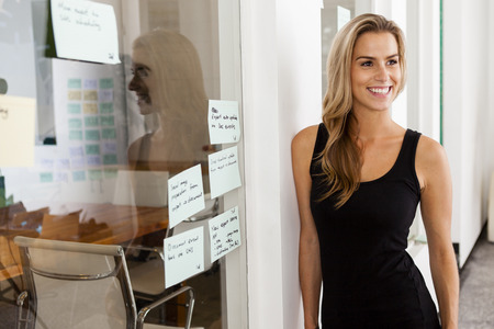 startup: Young woman entrepreneur in her startup office smiling Stock Photo