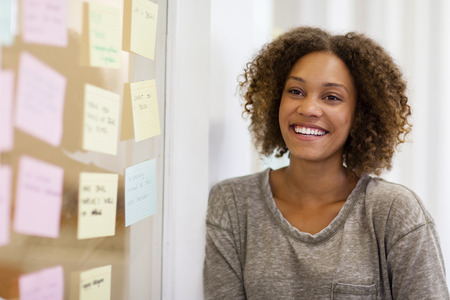 Woman entrepreneur smiling in front of her task cards on her office window