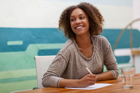 Young entrepreneur smiling while sitting at an office table Stock Photo