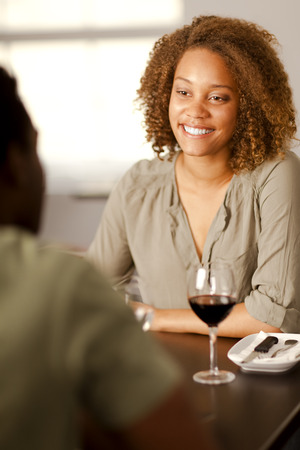 Happy young mixed-race woman smiling at her partner in a restaurant.