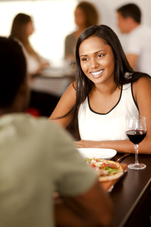 Beautiful young Indian woman smiling at her partner in a restaurant.