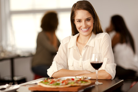 Portrait of a beautiful young woman looking to camera in a pizza restaurant.