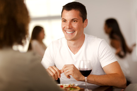 Handsome young man enjoying pizza with his girlfriend in a restaurant.