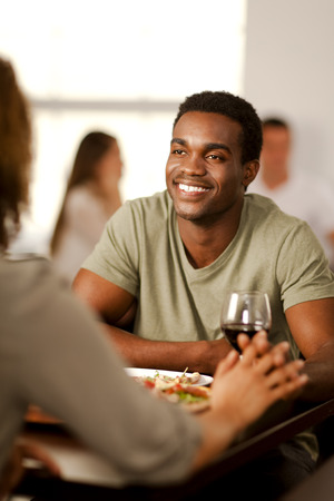 Handsome young African-American man holding hands with his girlfriend in a restaurant. Stock Photo