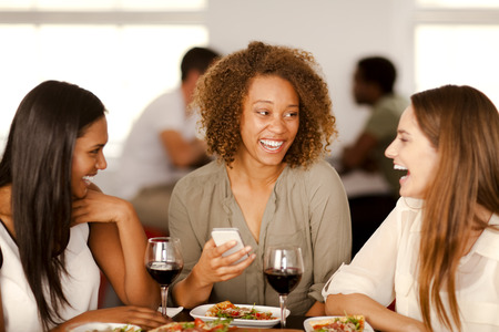 Group of mixed-race girls laughing in a pizza restaurant