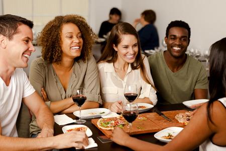 riendose: Grupo de raza mixta de amigos riendo juntos en un restaurante de pizza Foto de archivo