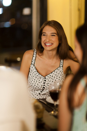 restuarant: Young woman laughing at a dinner with friends in a restuarant