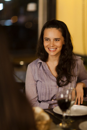 Young woman laughing at a dinner with friends in a restuarant
