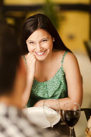 Beautiful young brunette woman smiling at her partner in a restaurant Stock Photo