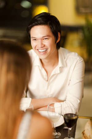Happy young Asian man smiling and laughing with friends in a restaurant