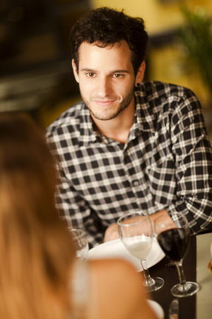 Happy young man smiling at his girlfriend in a restaurant