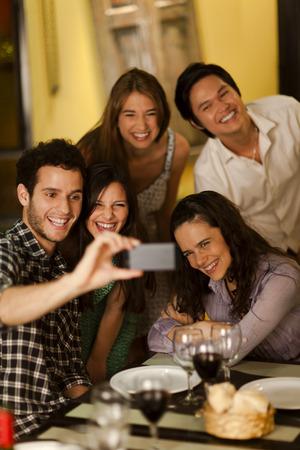 Groupe de jeunes adultes prenant une photo de Selfie dans un restaurant Banque d'images