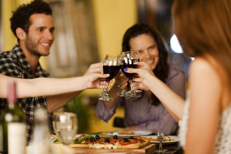 vino: Grupo de amigos brindando con vino en un restaurante