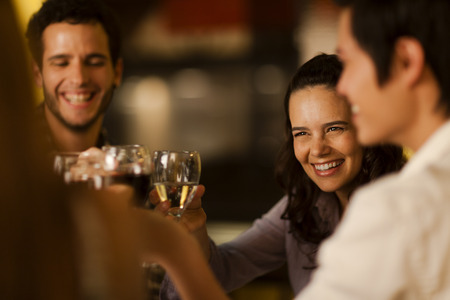 Group of friends toasting with wine at a restaurant Stock Photo
