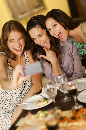 Three beautiful young women taking a selfie photo in a restaurant