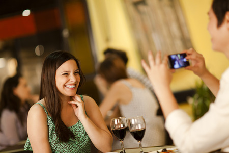 Beautiful young woman posing for a smartphone photo in a restaurant Stock Photo
