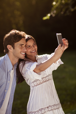 Beautiful young couple taking a selfie in a park in summer