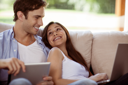 Young couple relaxing with a laptop and tablet computer together on a sofa
