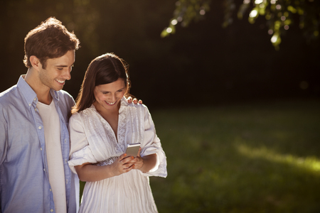 Beautiful young couple looking at a smartphone together outside