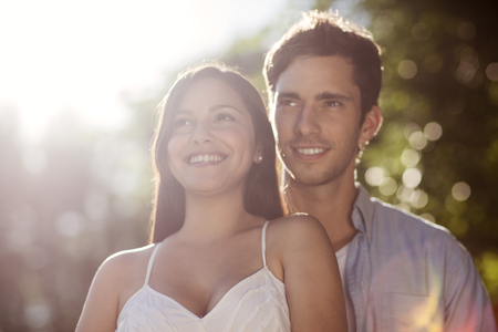 Beautiful young couple standing together outdoors in the sun Stock Photo