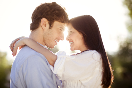 Young couple hugging outdoors in the sun