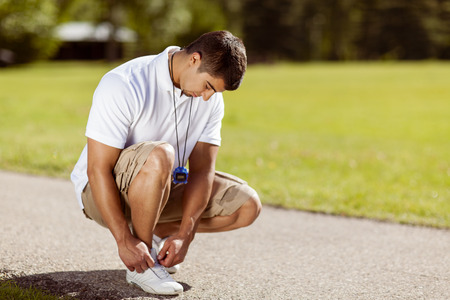 Fit young man with a stopwatch tying his shoelaces in the park.