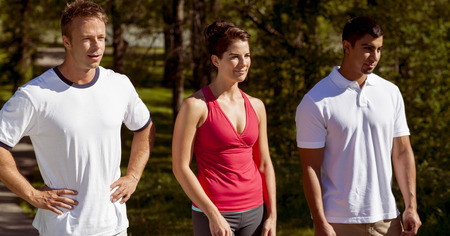 Three athletic friends stand side by side in the park. Stock Photo