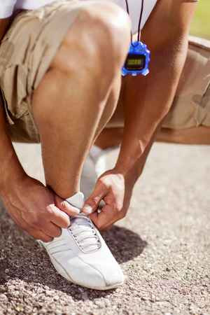 Fit man with a stopwatch tying his shoelaces. Stock Photo