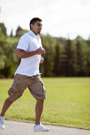 Young Hispanic man smiles while running through the park. Stock Photo