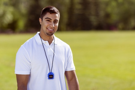 Physically fit young man smiles at the camera while wearing a stopwatch in the park.