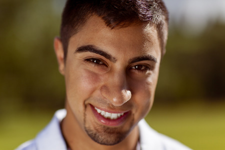 Handsome young Hispanic man smiles at the camera.
