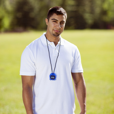 upper half: Physically fit young man smiles at the camera while wearing a stopwatch in the park.