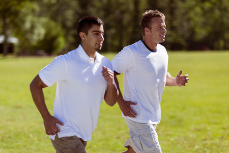 Two fit men job through the park together. Stock Photo