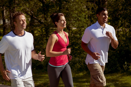 Three athletic friends jog together through the park.