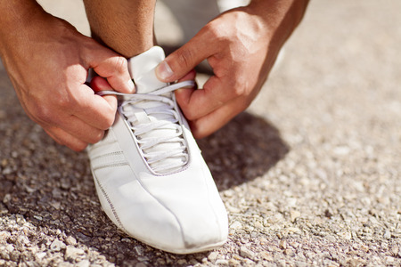 Man tying his shoelaces.