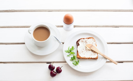 Table set for a typical breakfast with poached eggs, coffee and toast Banco de Imagens