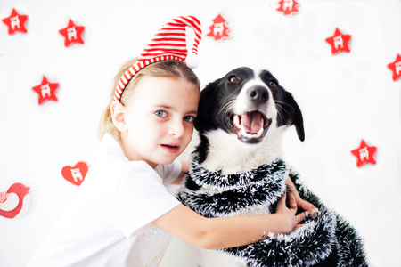Happy Little girl wearing a headband and dog at Christmas Stock Photo