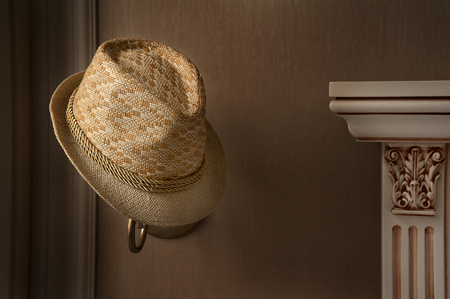 Stylish straw hat is hanging on the lamp . The window light falls on the left side to the straw muff and fireplace