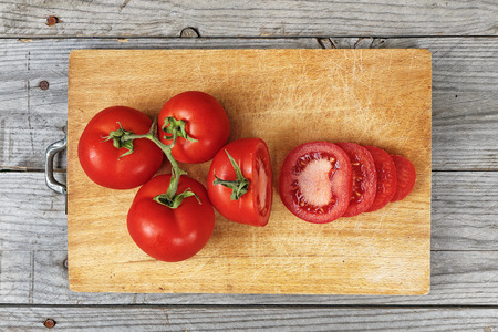 Close up of sliced tomato on wooden cutting board