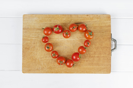 love heart tomato composition on wood background
