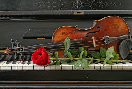 Old antique piano violin and red rose