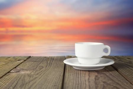 close up of white coffee cup on wooden table with landscape photo